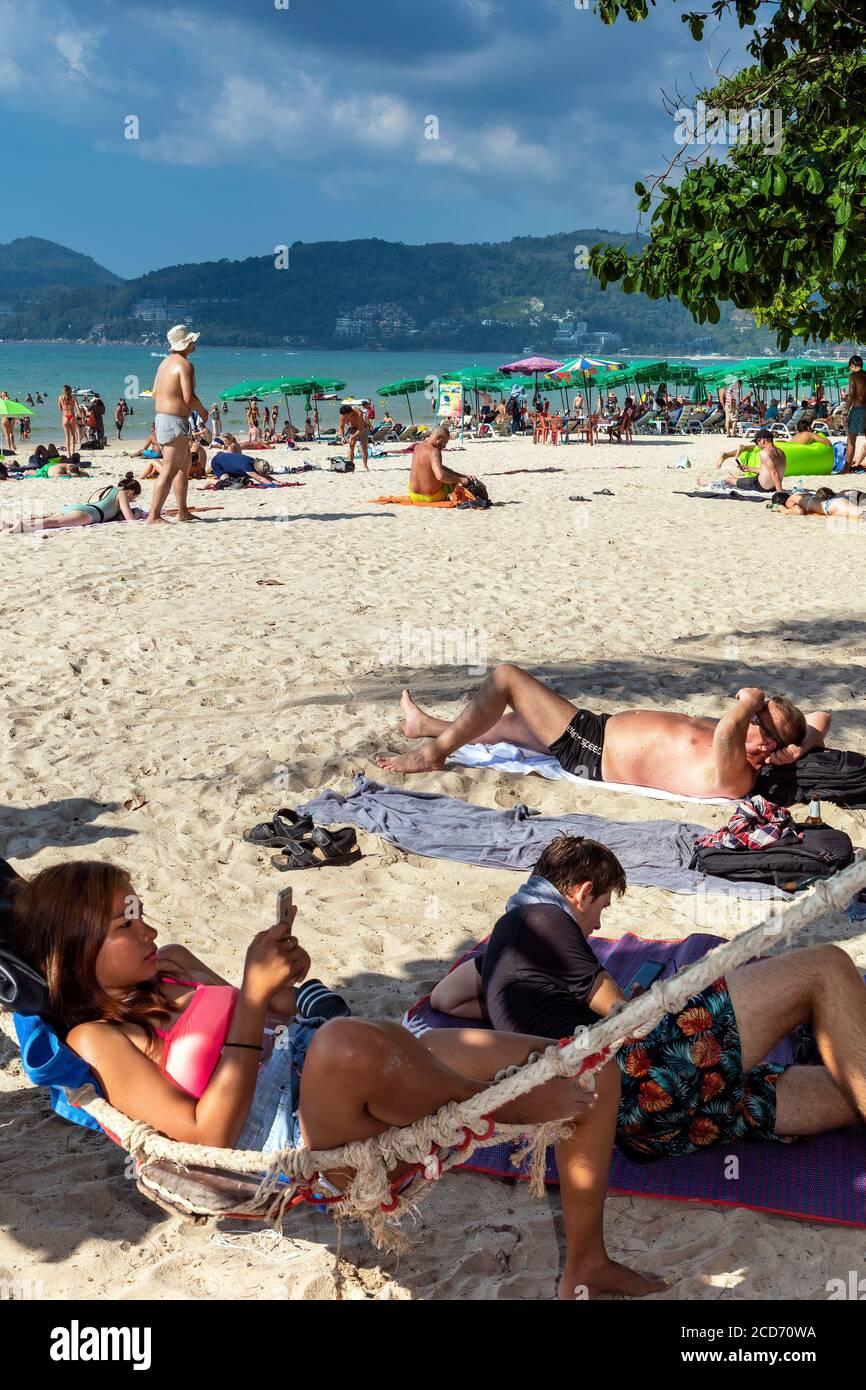 Turista in amaca usando un telefono mobile sulla spiaggia, Patong, Phuket, Thailandia Foto Stock