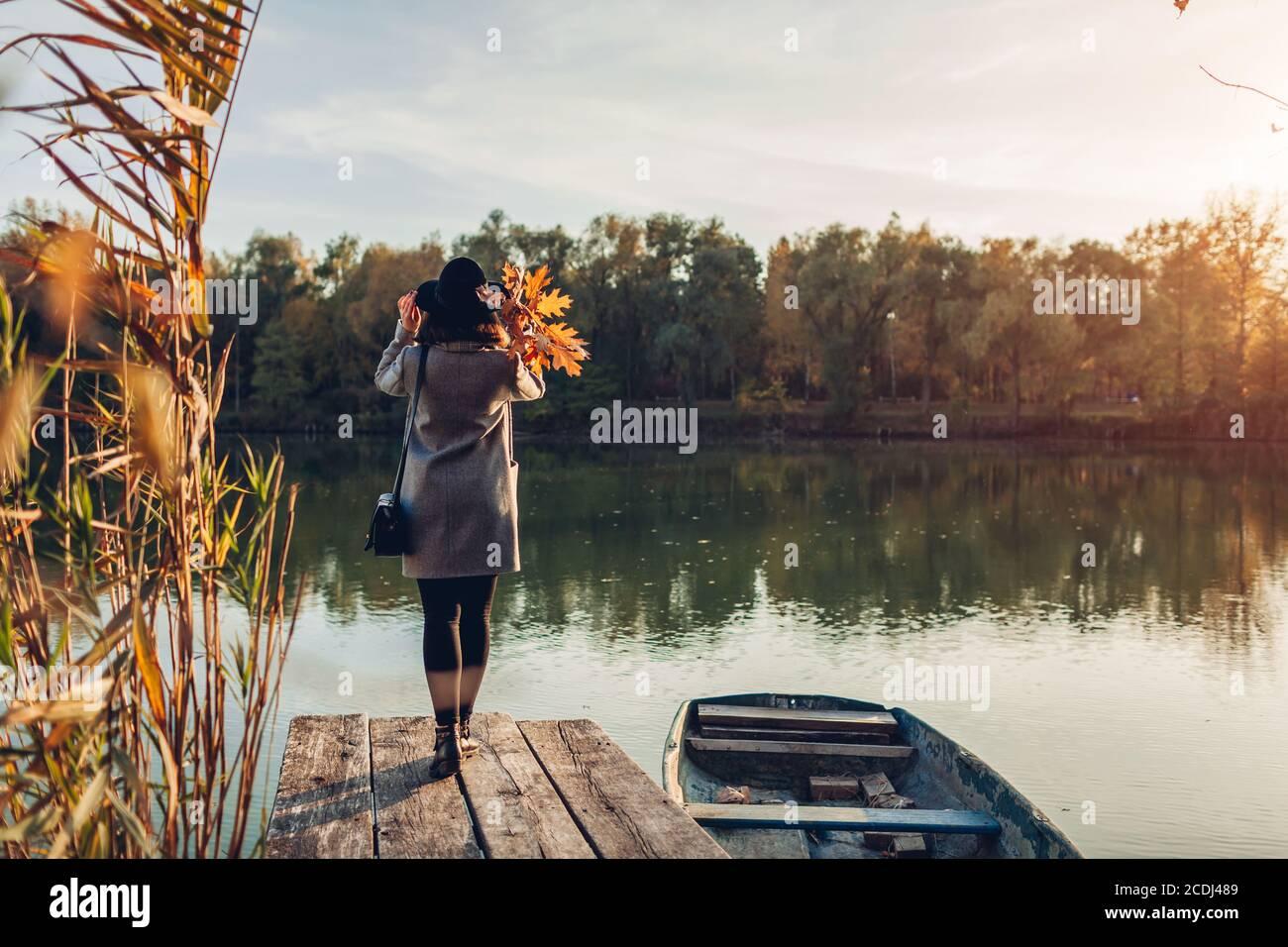 Donna che cammina sul molo del lago in barca ammirando il paesaggio autunnale che tiene le foglie. Attività della stagione autunnale Foto Stock