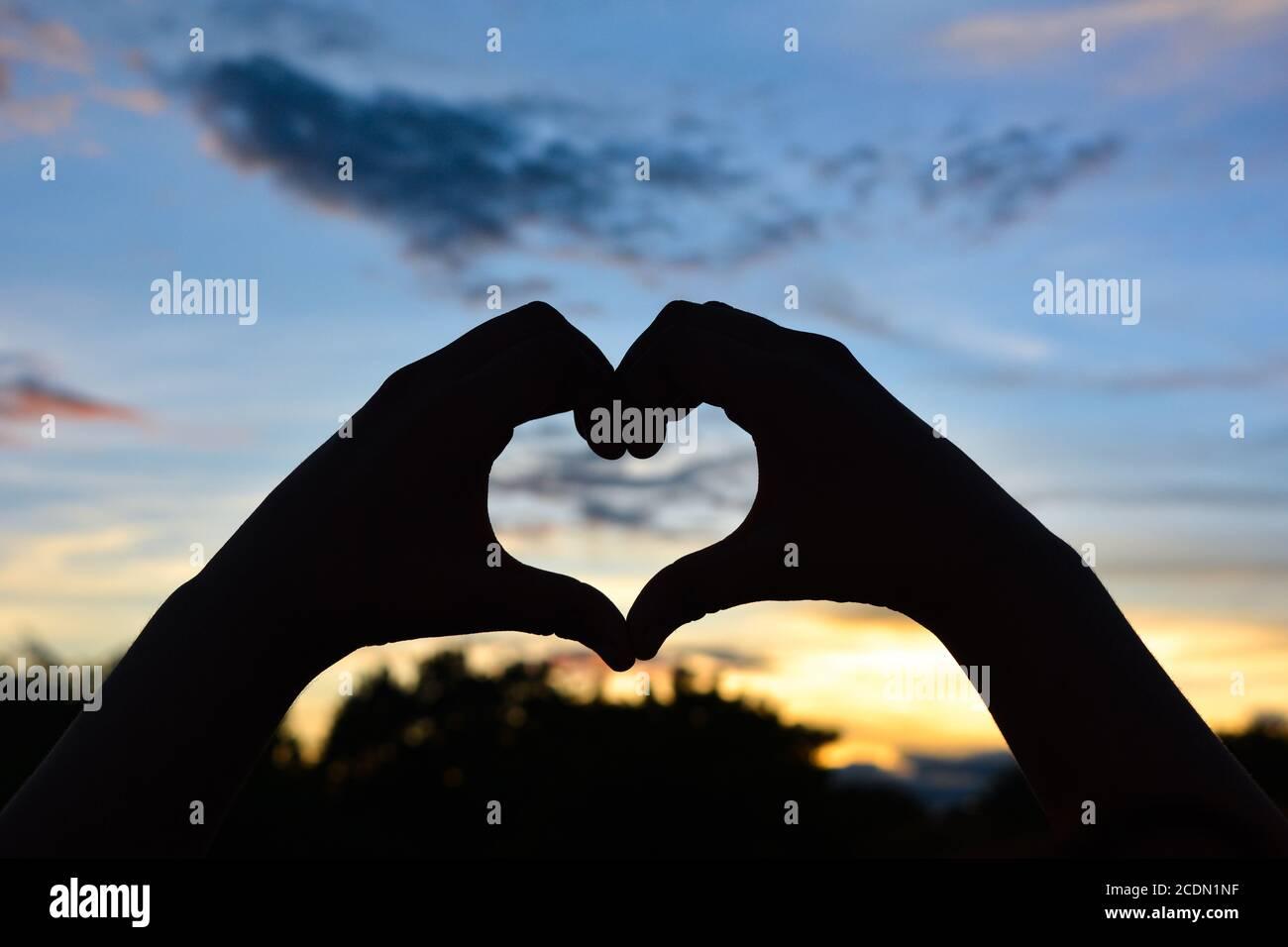 Silhouette a forma di cuore con tramonto, concetto di San Valentino. Foto Stock