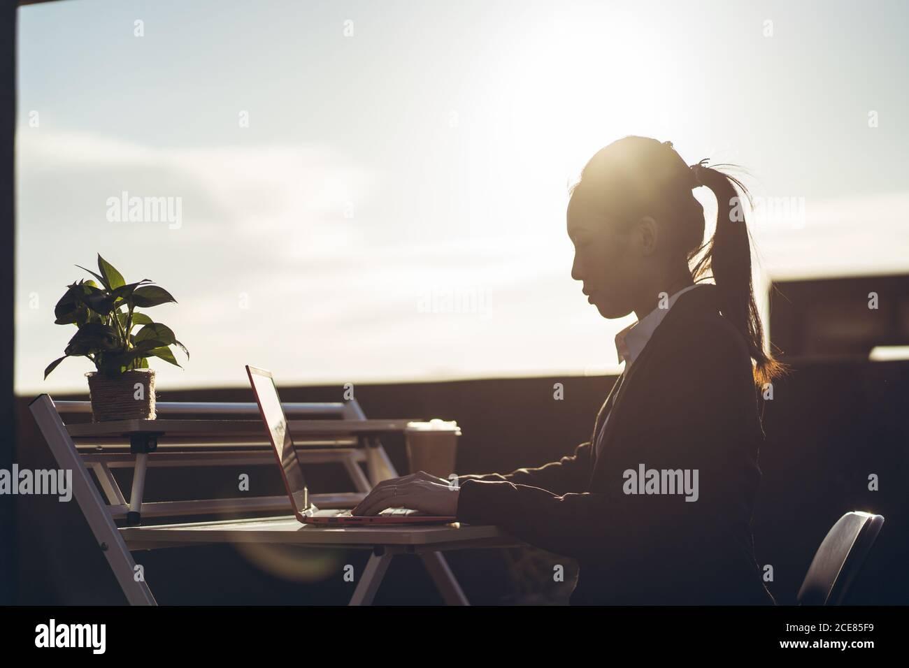 Vista laterale della giovane donna asiatica d'affari in abiti formali utilizzo di un computer portatile mentre si lavora in remoto sulla terrazza panoramica della città Foto Stock