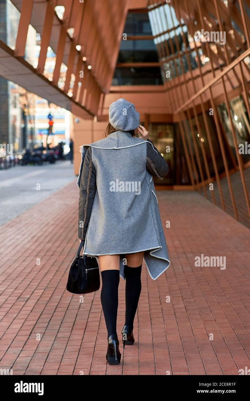 Vista posteriore di una donna imprenditore ben vestito che cammina lungo futuristico creazione e discussione di problemi aziendali sullo smartphone Foto Stock
