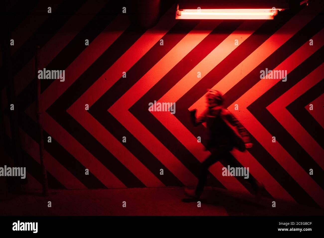 Vista laterale del movimento immagine sfocata del maschio che cammina verso il basso nel tunnel in direzione opposta al grande rosso e nero frecce sulla parete illuminate da luci rosse Foto Stock