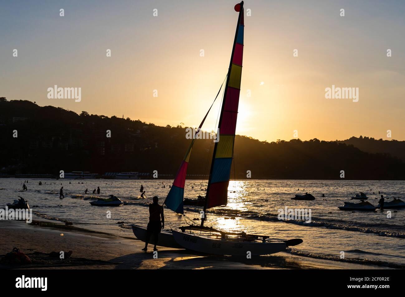 Barca a vela a noleggio a Patong Beach al tramonto, Phuket, Thailandia Foto Stock