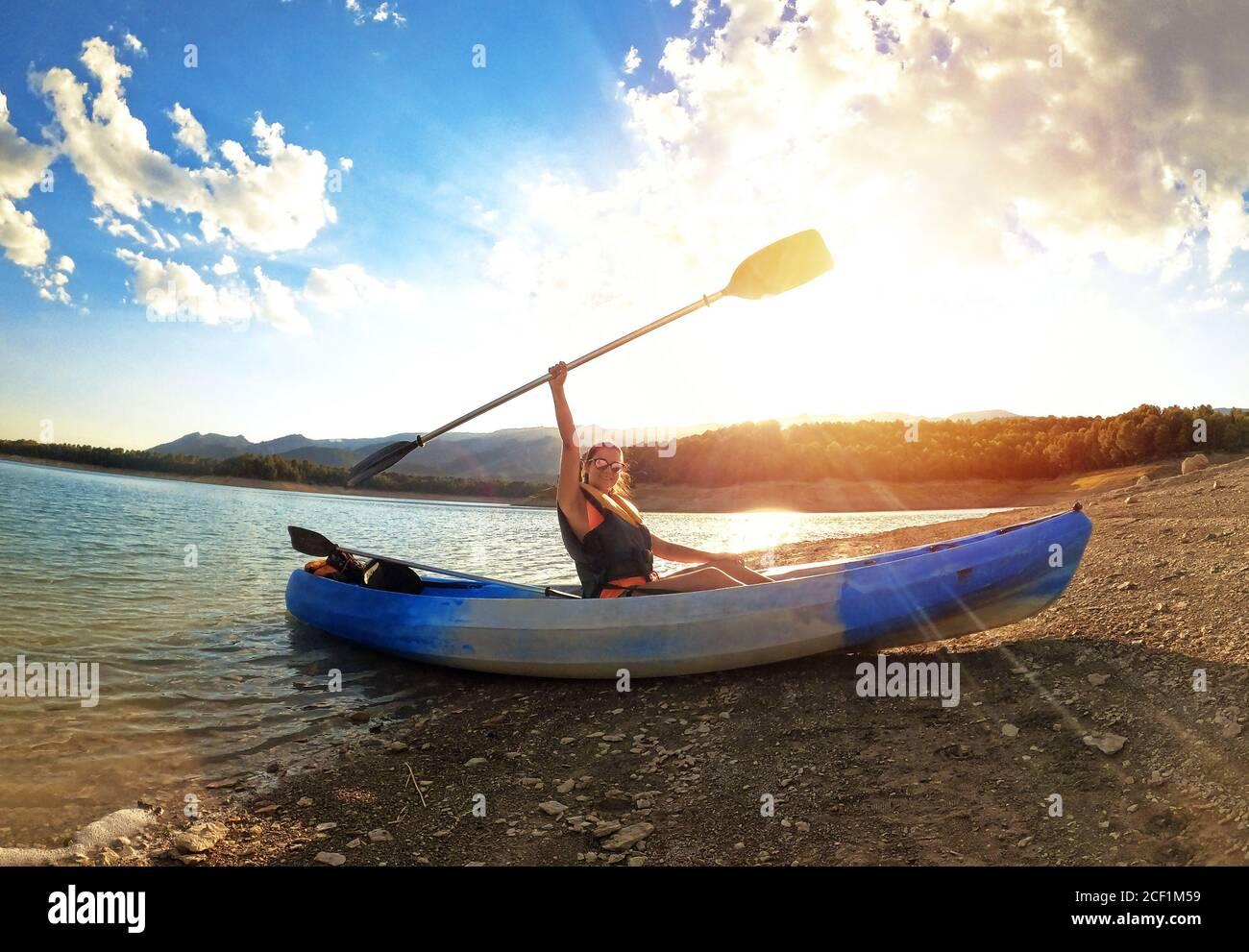 Donna in kayak canottaggio al mare contro il tramonto a Embalse de la Bolera, Jaen, Spagna. Il successo sul concetto di obiettivi sportivi. Potere della donna. Foto Stock