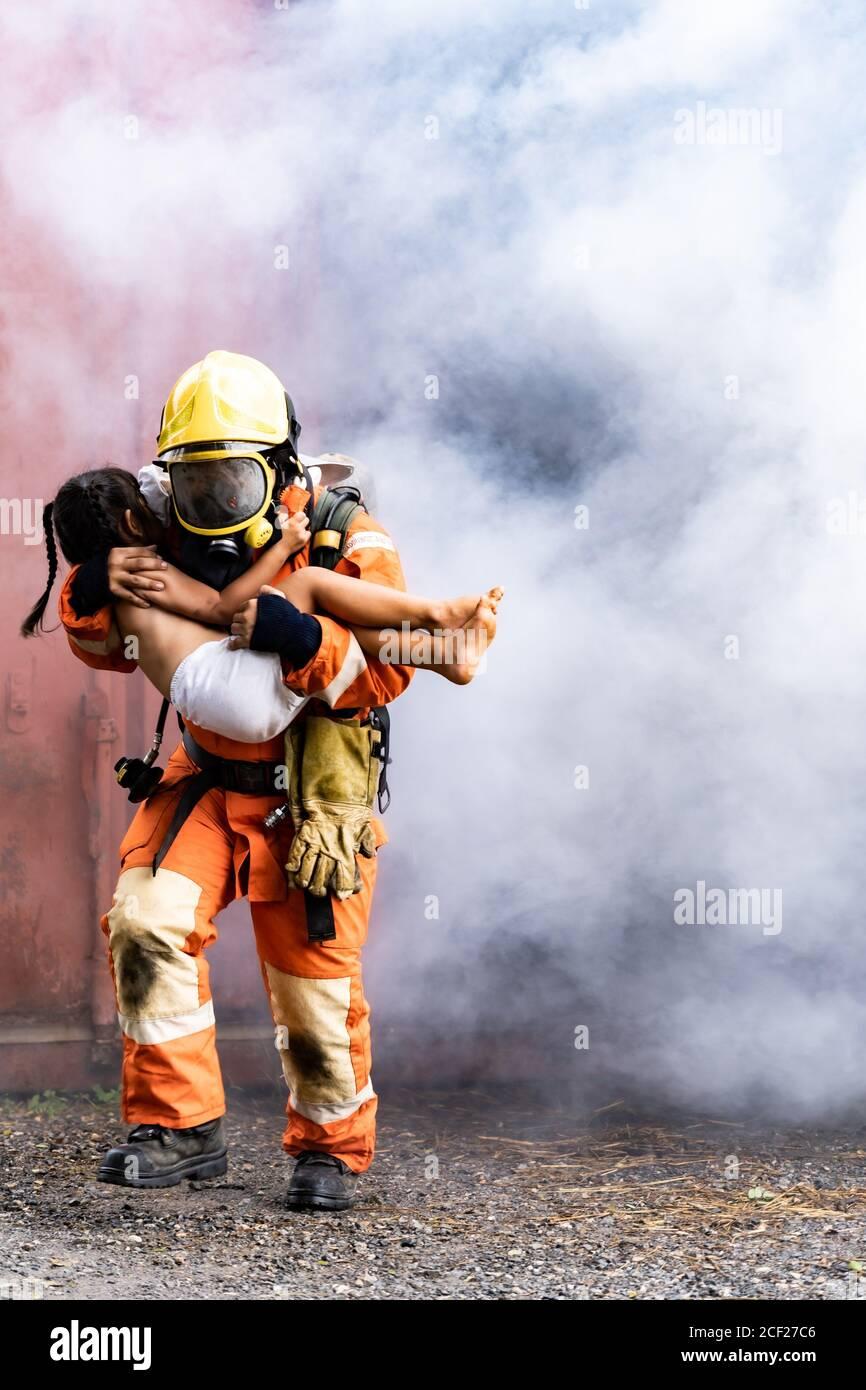 Pompiere salvataggio ragazza bambino piccolo da costruzione in fiamme. Tiene la ragazza e scava fuori attraverso il fumo dalla costruzione. Soccorso di sicurezza dei vigili del fuoco da Foto Stock
