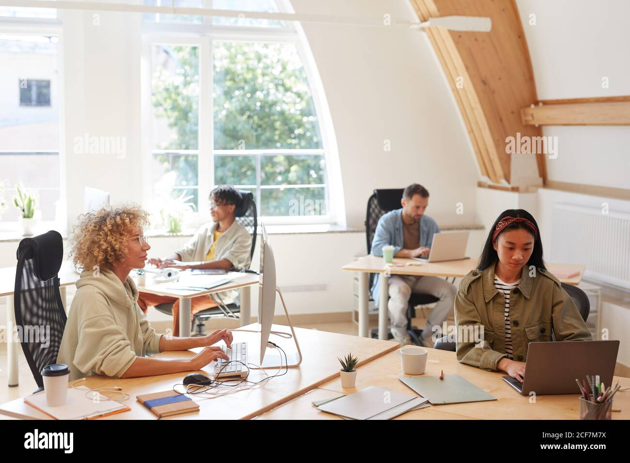 Gruppo di uomini d'affari in abbigliamento casual seduti al loro luoghi di lavoro e utilizzo di computer nel proprio lavoro in ufficio Foto Stock
