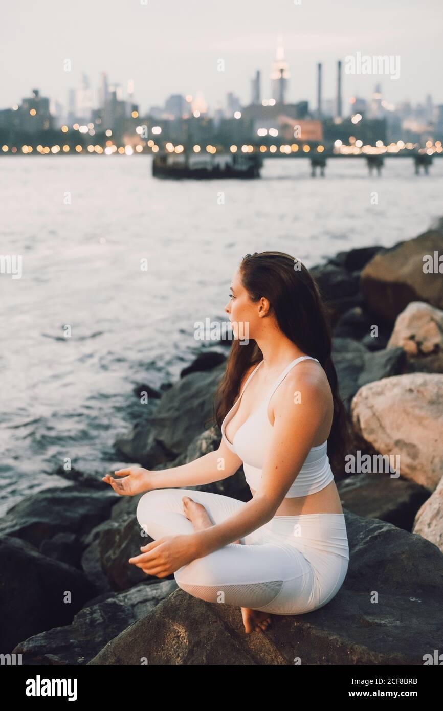 Vista dall'alto laterale di una femmina concentrata in attività seduta sulla pietra sul lungomare mentre si pratica yoga sullo sfondo di il paesaggio urbano serale e lo sguardo lontano Foto Stock