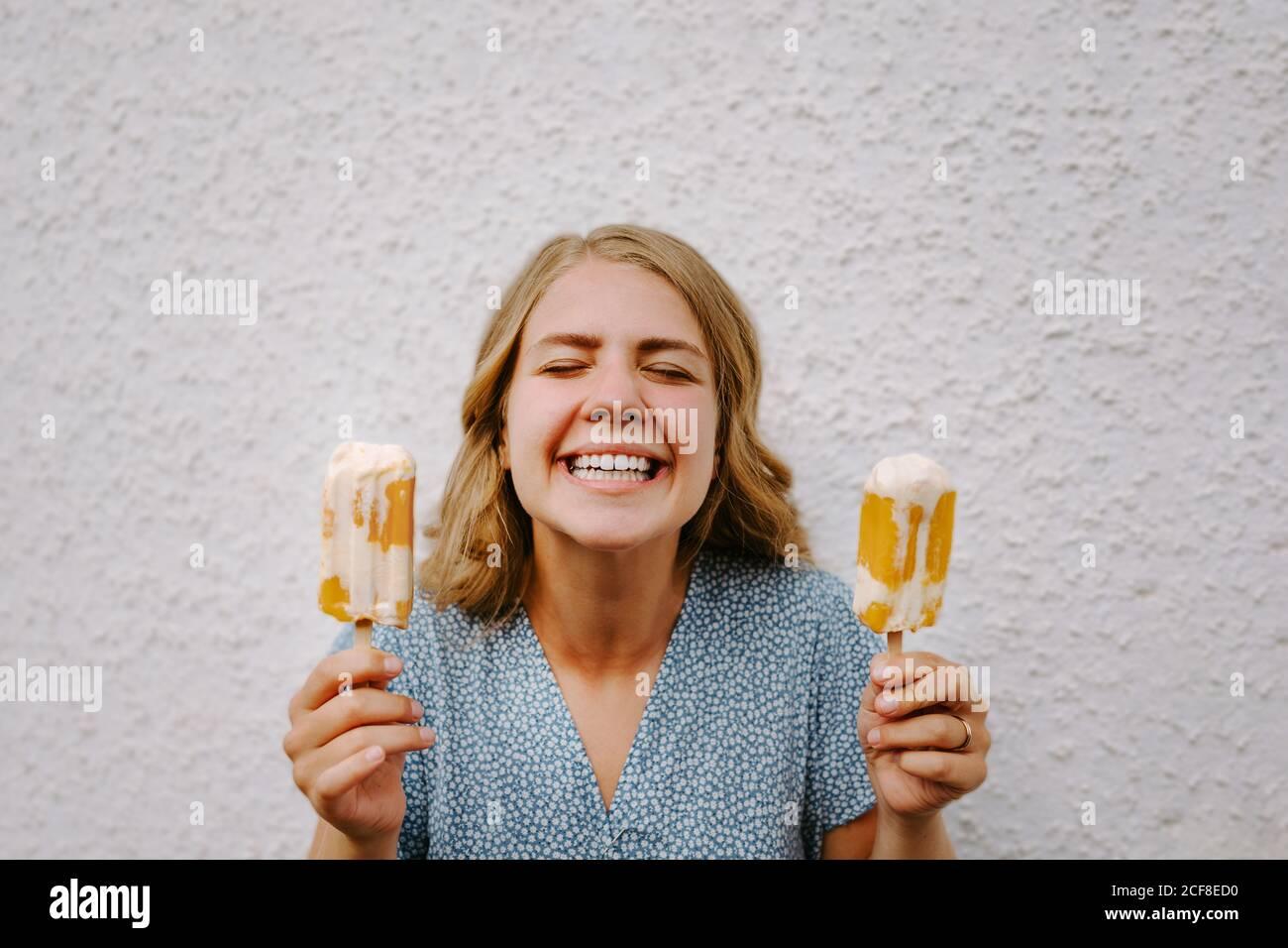 Femmina con gli occhi chiusi facendo simpatici grimace volti con gustoso lecci di ghiaccio su bastoni su sfondo bianco Foto Stock