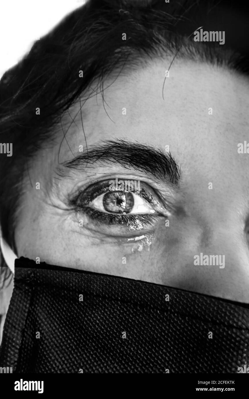 Primo piano di una donna triste che piange in maschera protettiva con lacrime, dolore agli occhi durante la pandemia globale del coronavirus. Foto Stock