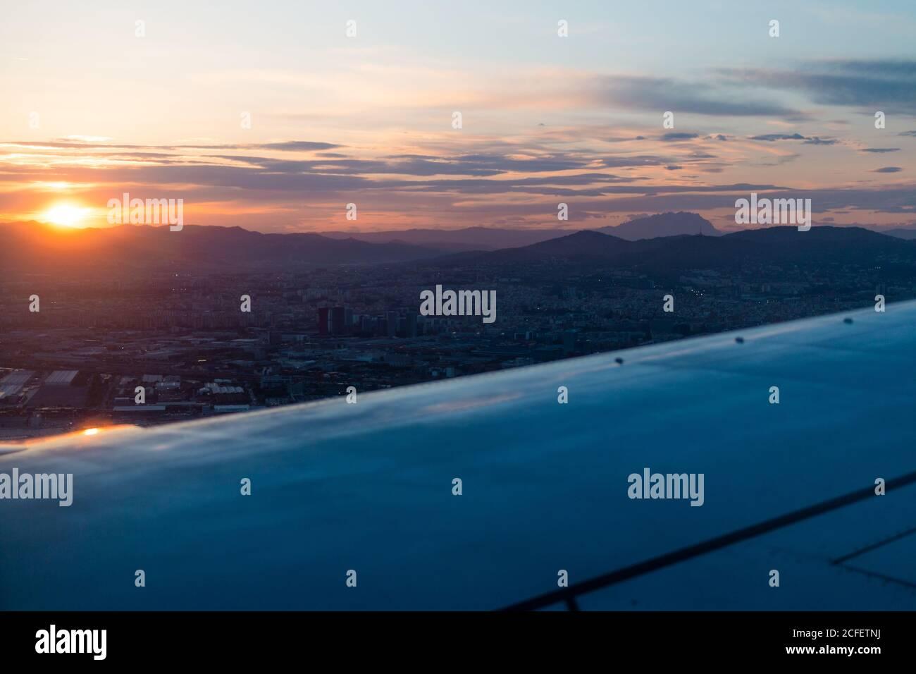 Vista dalla finestra dell'ala di un moderno aeromobile che sorvola dense nuvole durante il tramonto Foto Stock