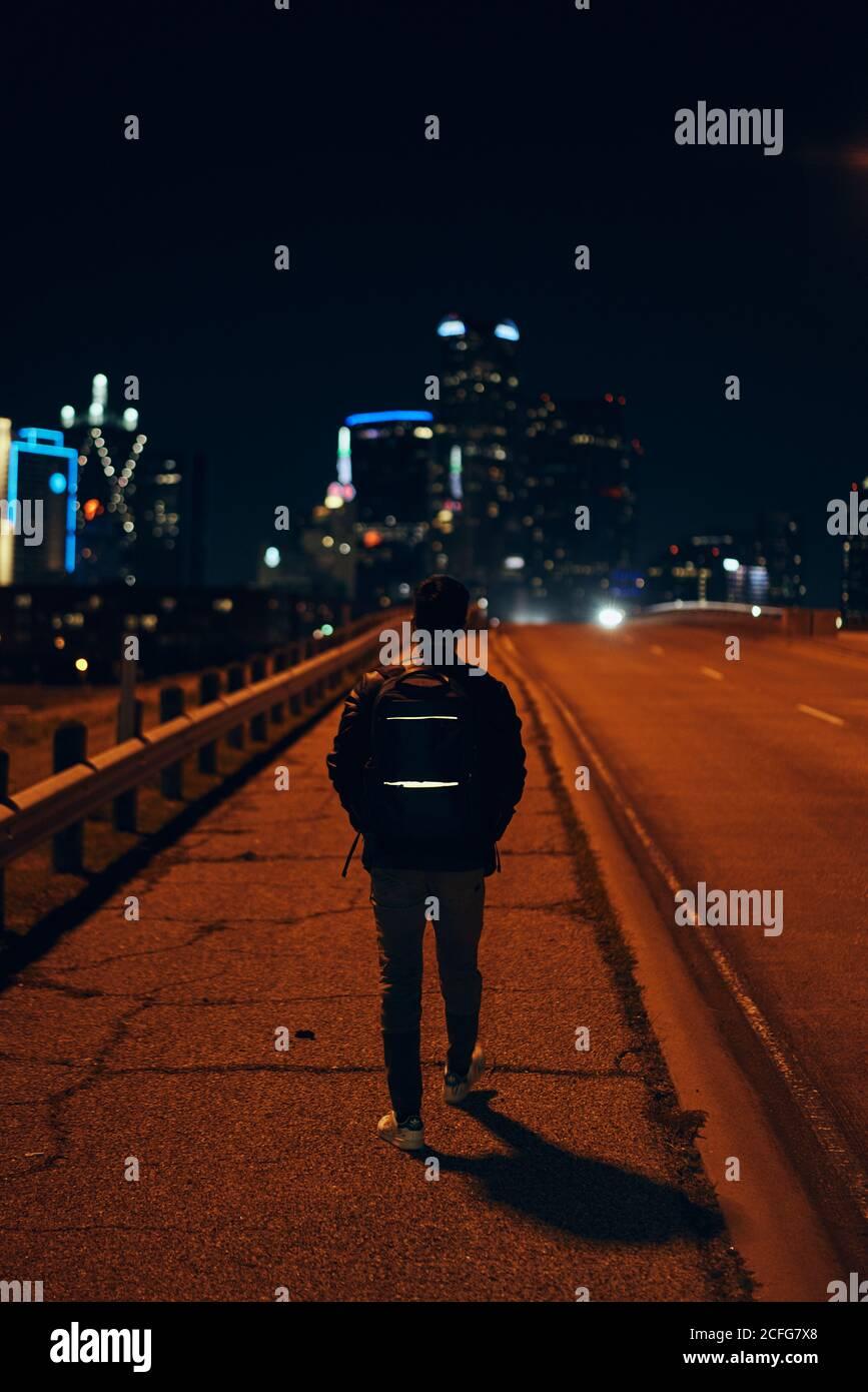 Vista posteriore di un uomo anonimo in giacca casual in pelle nera con zaino che cammina nella città notturna su sfondo sfocato Foto Stock