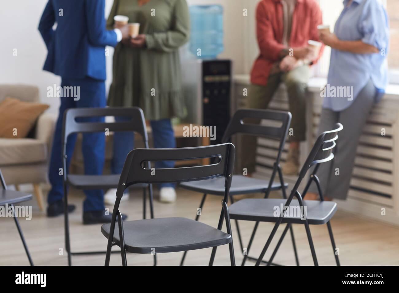 Ripresa tagliata di sedie vuote in cerchio durante la riunione di gruppo di supporto con le persone che chiacchierano in background, spazio di copia Foto Stock