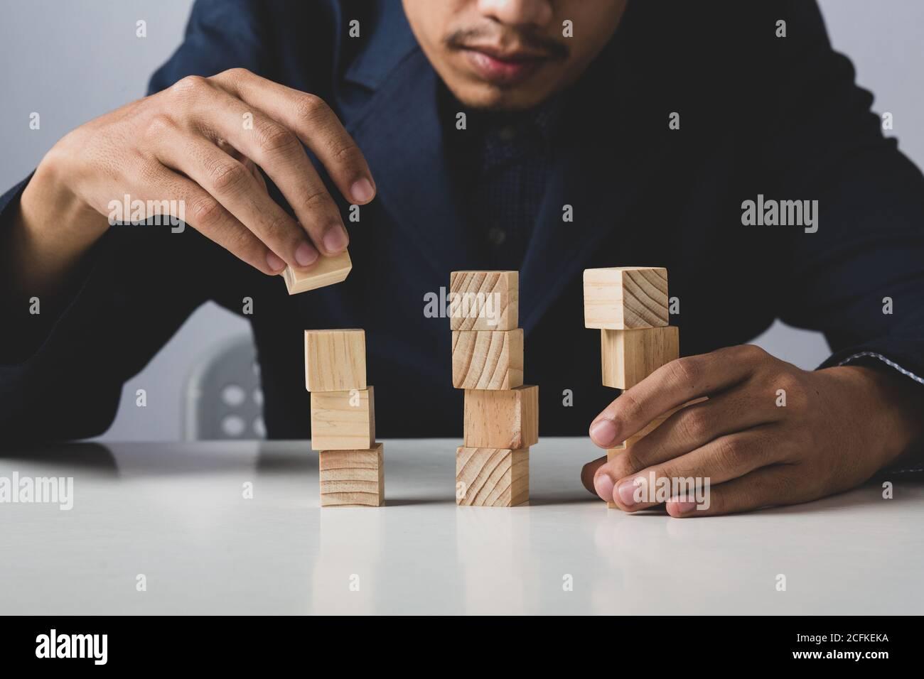 Mani di imprenditore uomo d'affari che tiene blocchi di legno che mettono ad una struttura, concetto di lavoro di squadra, strategia, lavoro professionale di manager per executiv Foto Stock