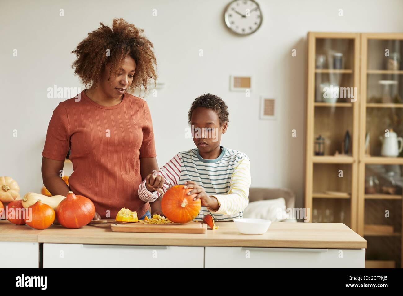 Giovane donna afroamericana adulta che indossa abiti casual in piedi a. tavola guardando il suo bambino che intagliano la zucca Foto Stock