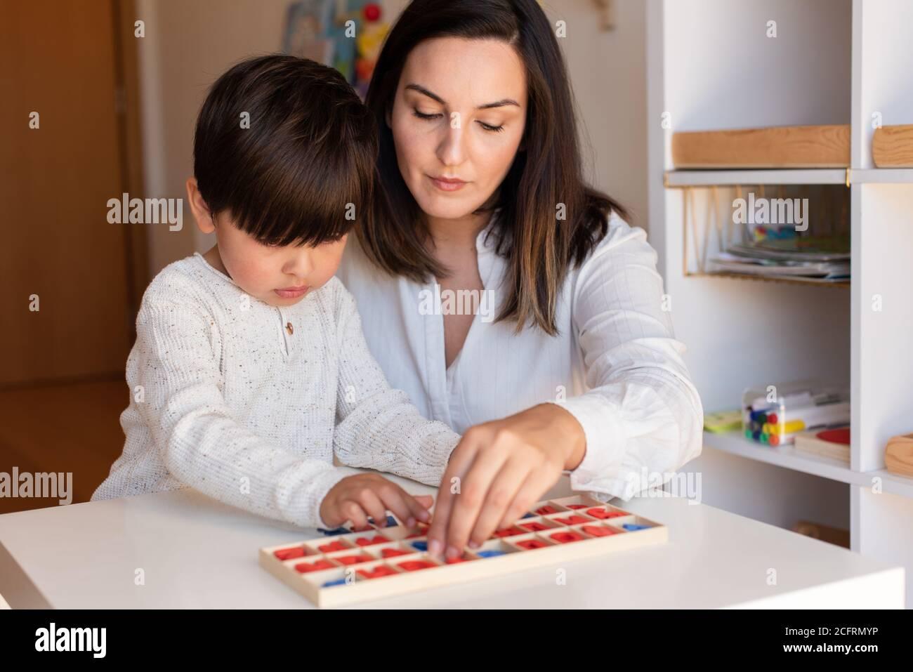 Lillte Kid imparare a scrivere e leggere con un alfabeto e la madre o l'aiuto dell'insegnante. Homeshooling. Comunità di apprendimento. Scuola Montessori Foto Stock