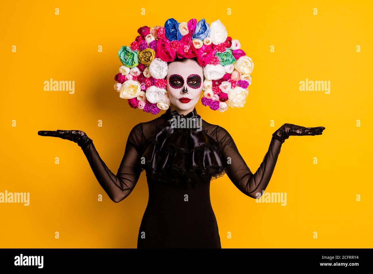 Foto di simpatica giovane signora paurosa guardare le mani tenere spazio vuoto proporre speciali oggetti tradizionali indossare abito nero morte rose in costume di carnevale Foto Stock