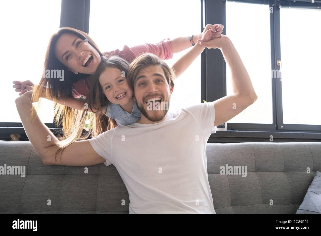 Felici genitori allegri che si divertono con le figlie carine che giocano sul divano Foto Stock