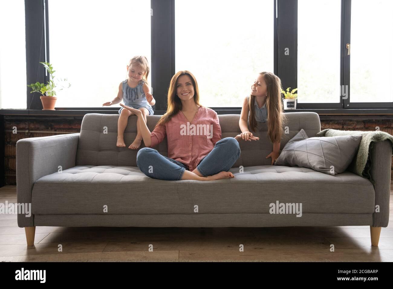 Donna calma che si concentra sugli esercizi di yoga sul divano a casa, mentre due bambini rumorosi ridere, correre Foto Stock