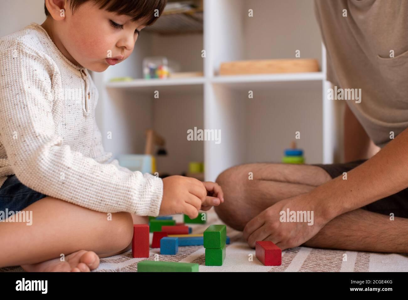 Piccolo capretto e suo padre che giocano a casa con i blocchi di costruzione di legno. Homeschooling. Rimani a casa. Tempo di famiglia Foto Stock