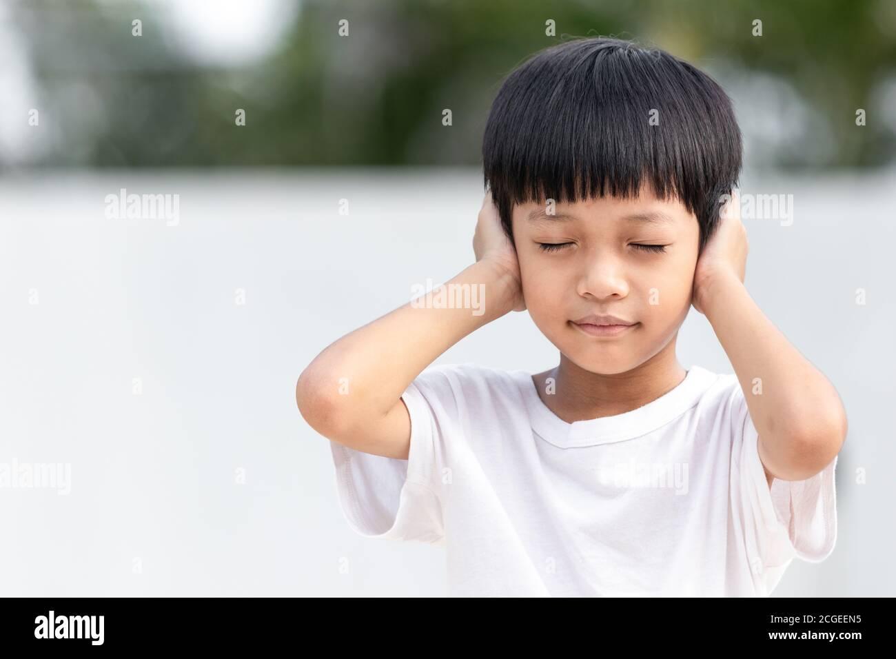 Il bambino asiatico gli coprì l'orecchio. Concetto di violenza familiare domestica. Bambino triste e infelice. Foto Stock