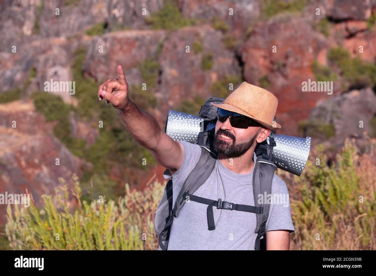 Uomo ispanico trekking con occhiali da sole sorridente e che indica il telaio Foto Stock