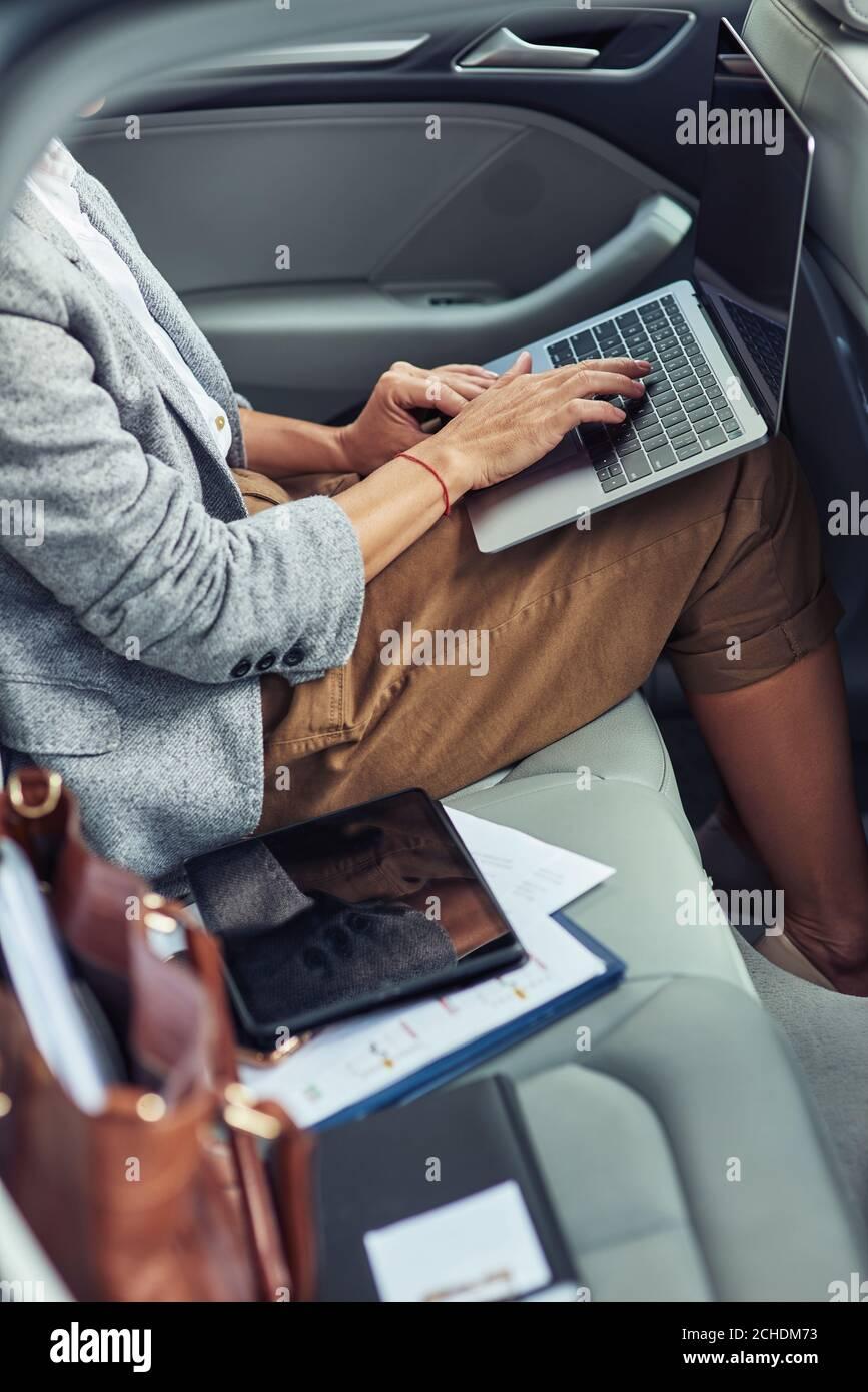 Lavorando online in taxi, foto verticale di donna d'affari utilizzando il computer portatile mentre si siede sul sedile posteriore in auto Foto Stock