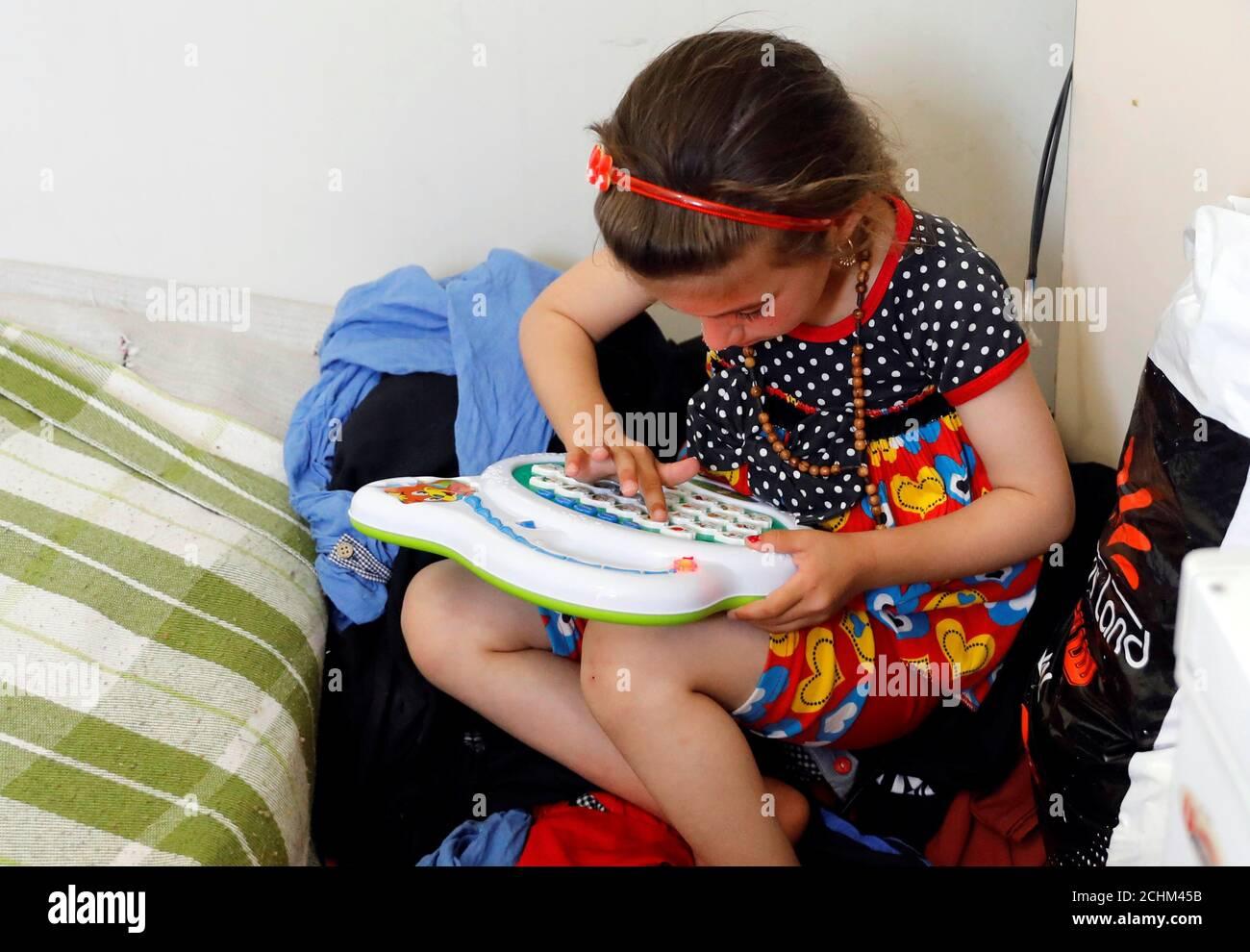 L'iracheno Christina Ezzo Abada, ex ostaggio di militanti dello Stato islamico per tre anni, gioca all'interno di una casa ristretta in un campo profughi di Erbil, Iraq, 10 giugno 2017. REUTERS/Erik De Castro Foto Stock