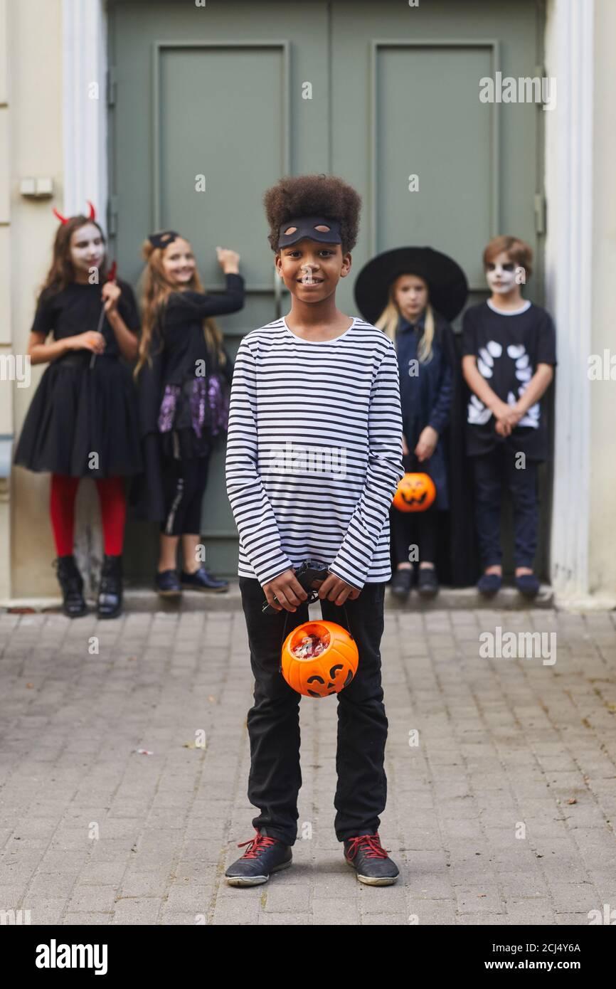Ritratto verticale a lunghezza intera di un gruppo multietnico di bambini che indossano costumi di Halloween guardando la macchina fotografica mentre trick o trattando insieme, concentrarsi sul ragazzo afroamericano in primo piano Foto Stock