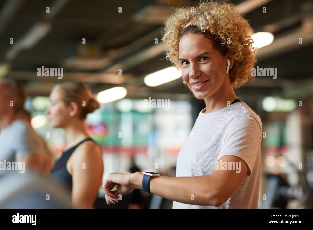 Ritratto di donna matura con capelli ricci che sorridono alla macchina fotografica durante l'allenamento, controlla il polso sull'orologio da polso Foto Stock