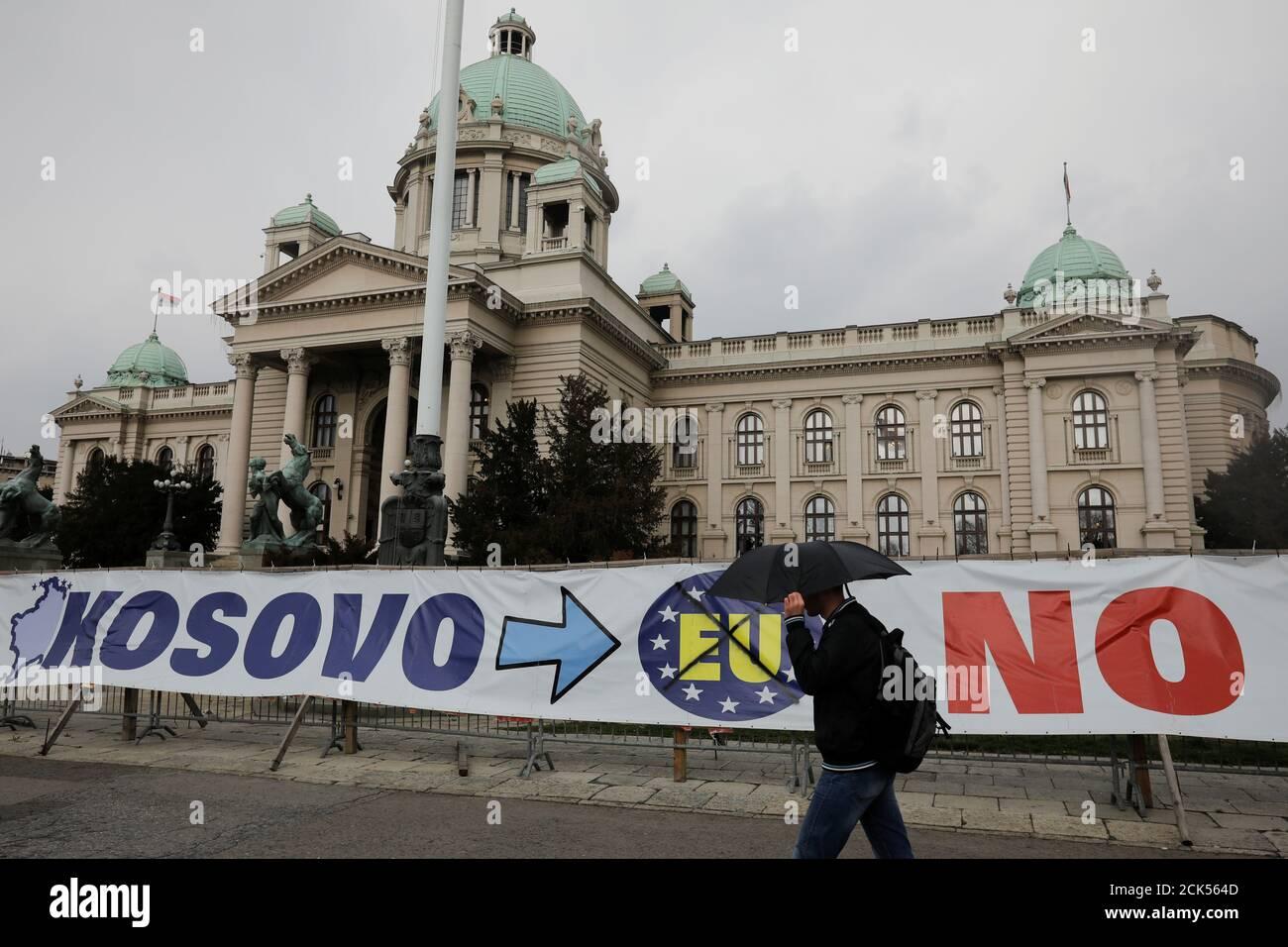 Un uomo passa davanti a un cartello di fronte all'edificio del parlamento serbo nel centro di Belgrado, Serbia, 27 marzo 2018. REUTERS/Marko Djurica Foto Stock