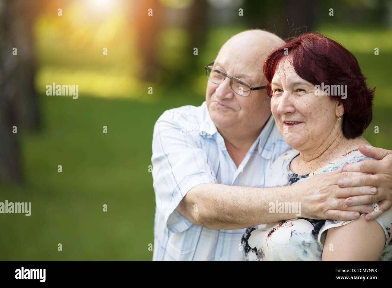 Felice coppia anziana in una passeggiata. Bei cittadini anziani, uomini e donne. Marito e moglie di vecchiaia sullo sfondo della natura. Foto Stock