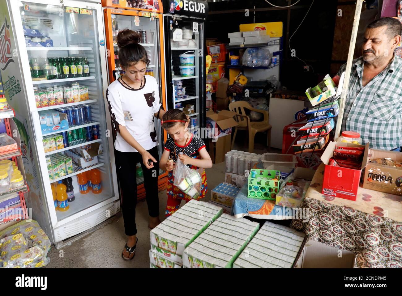 L'iracheno Christina Ezzo Abada, ex ostaggio di militanti dello Stato islamico per tre anni, acquista gelati in un negozio locale in un campo profughi a Erbil, Iraq, 10 giugno 2017. REUTERS/Erik De Castro Foto Stock