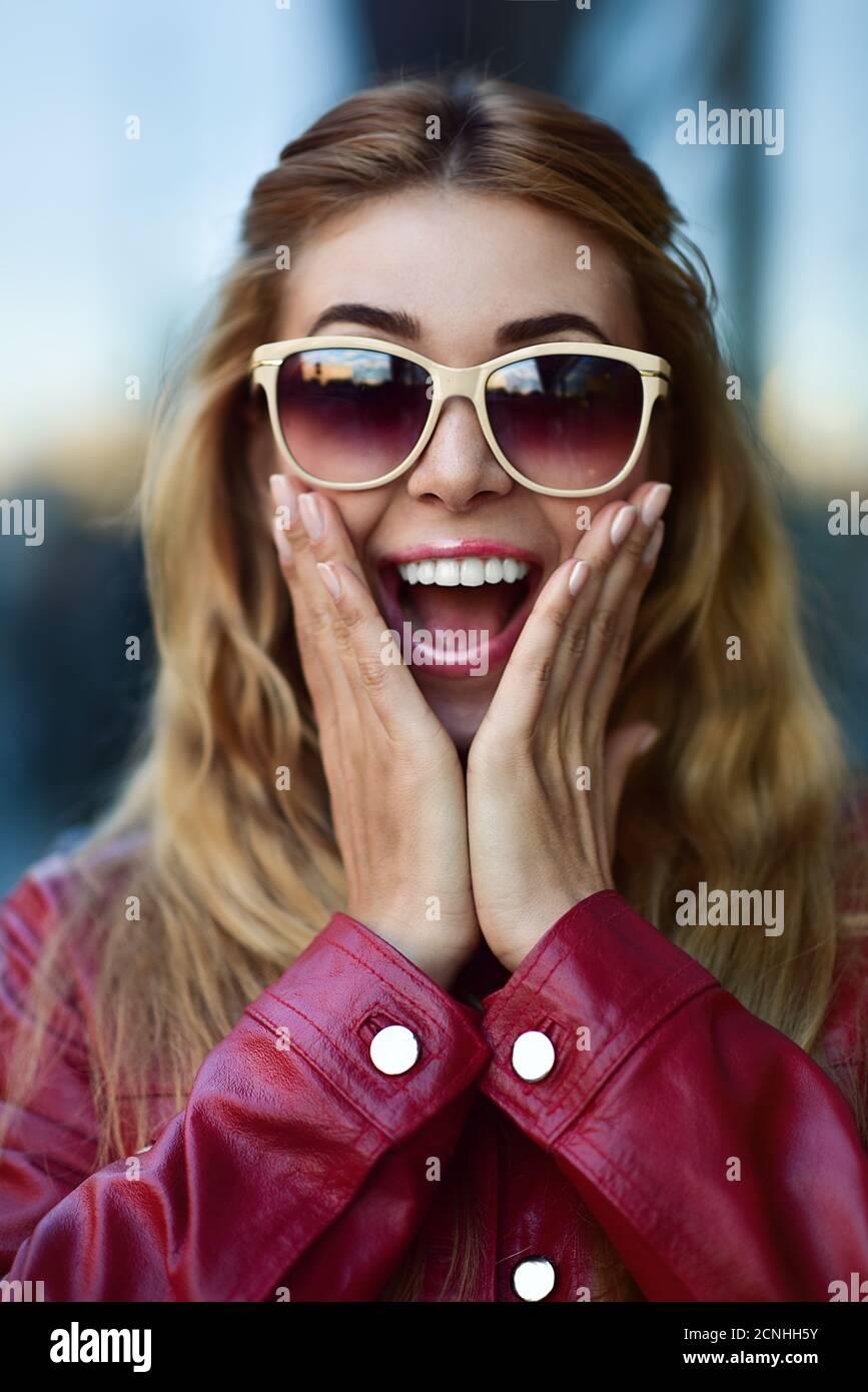Primo piano ritratto di una bella ragazza sorridente in occhiali da sole con denti piacevoli divertirsi in strada. Foto Stock