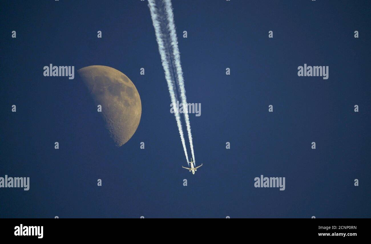 An aircraft flies past the moon over Anterselva, northwest Italy, January 23, 2010. REUTERS/Alessandro Bianchi (ITALY - Tags: TRANSPORT ENVIRONMENT IMAGES OF THE DAY) Foto Stock