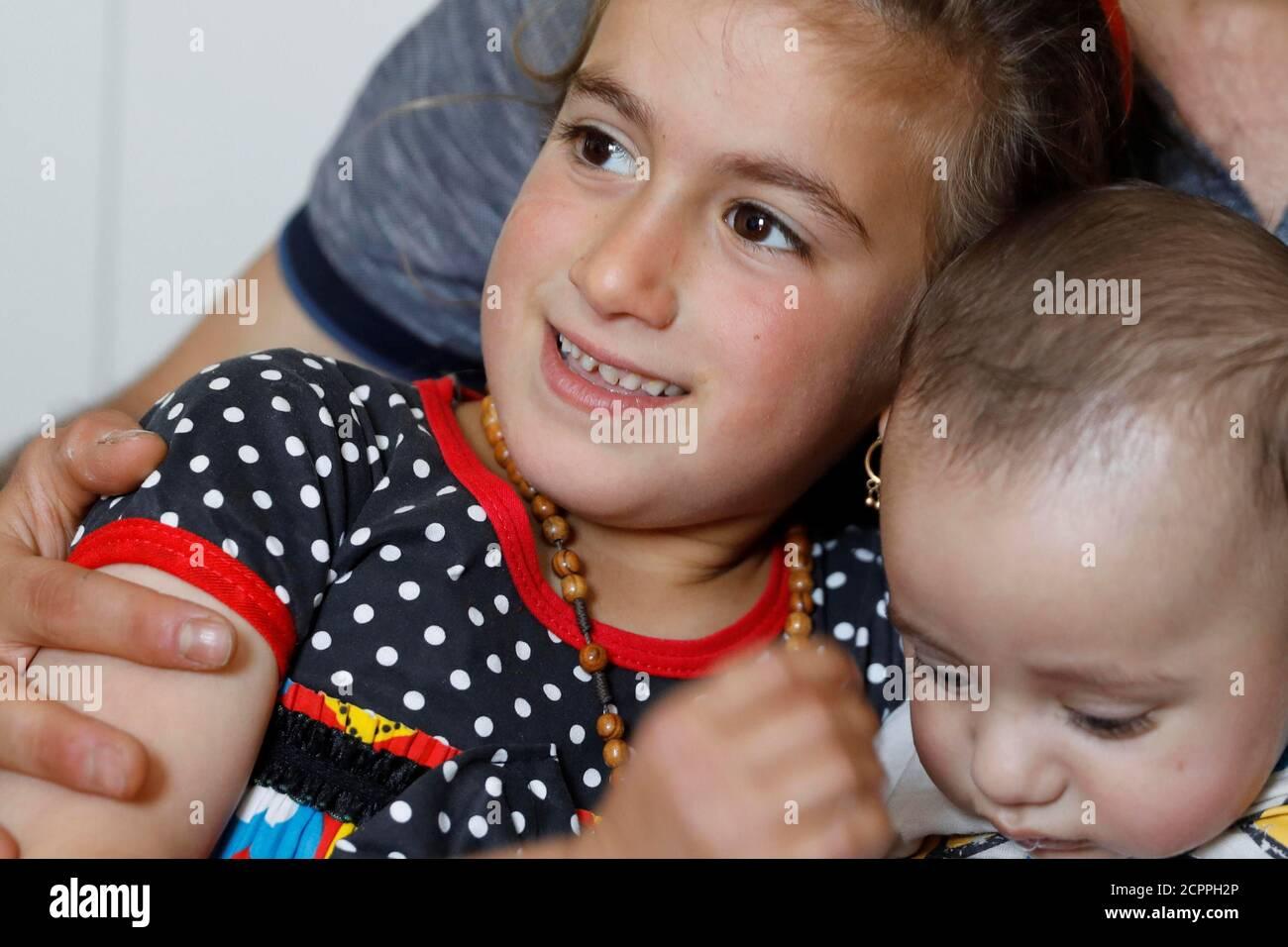 Christina Ezzo Abada irachena, ex ostaggio di militanti dello Stato islamico per tre anni, sorride mentre posa con suo fratello e nipote in una casa ristretta in un campo profughi a Erbil, Iraq, 10 giugno 2017. REUTERS/Erik De Castro Foto Stock