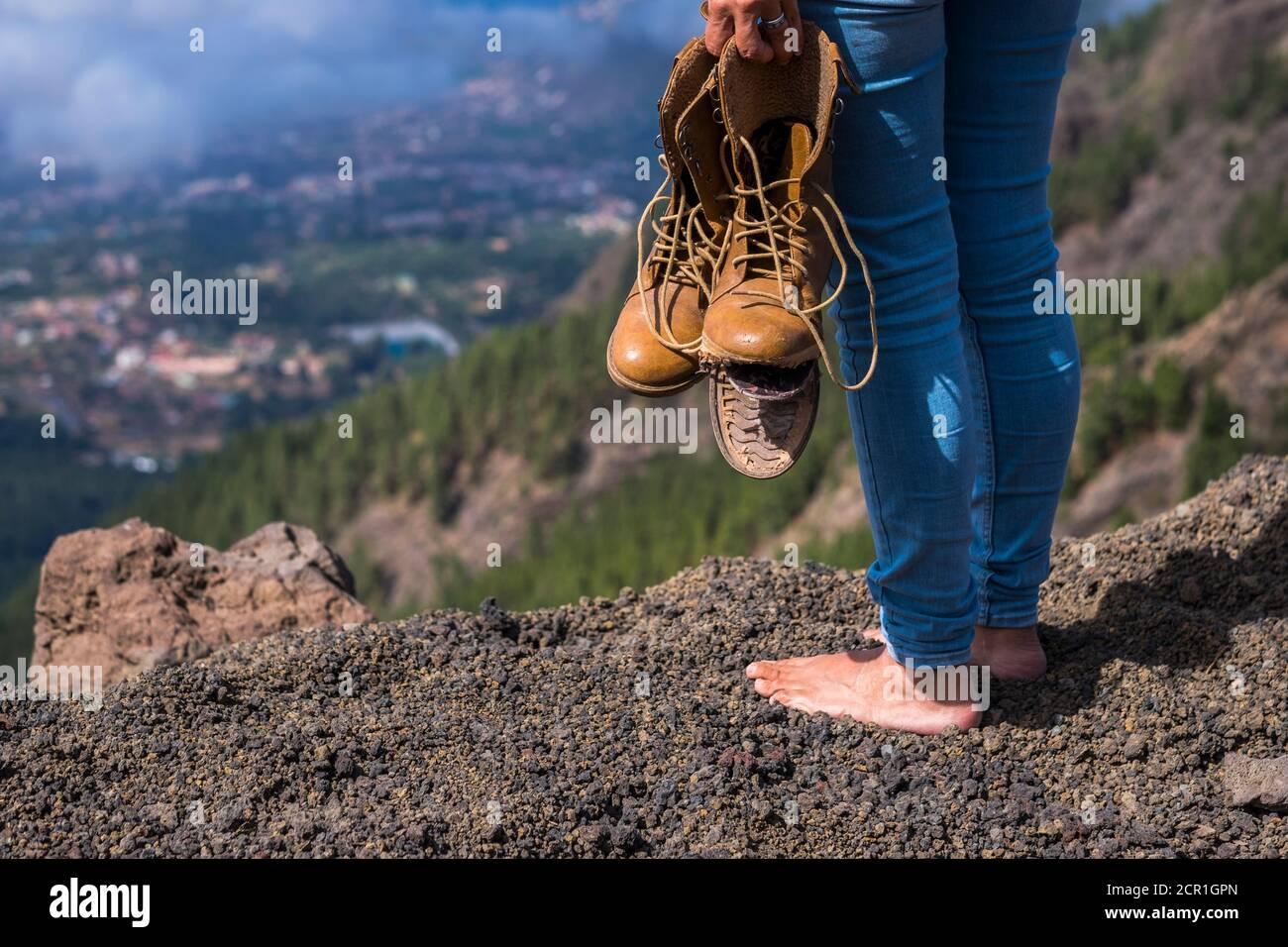 Concetto di stile di vita di viaggi e vanderlust con donna a piedi nudi stare in piedi con scarpe rotte sulle mani guardando la vista sulla cima della montagna Foto Stock