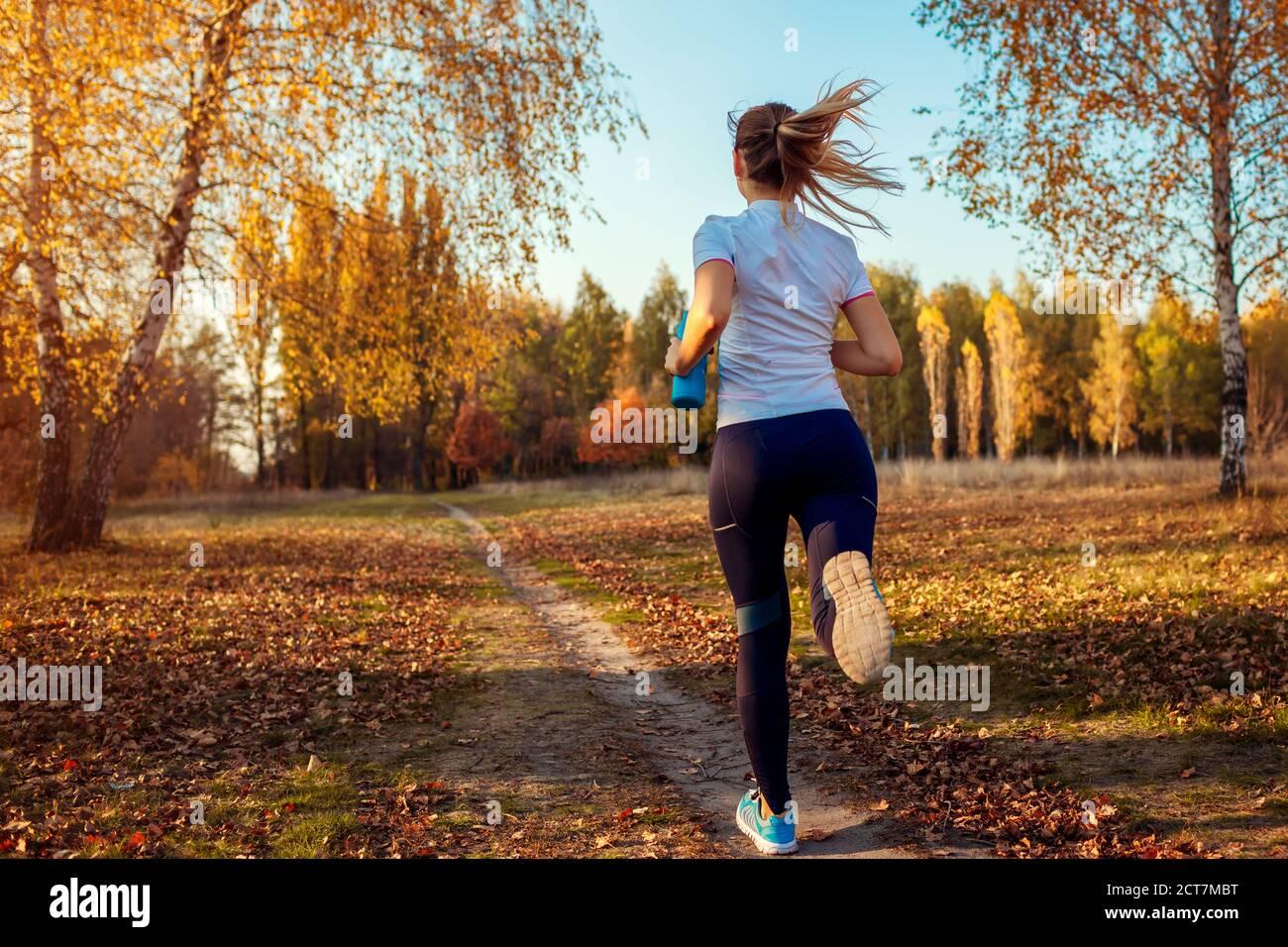 Allenamento dei corridori nel parco autunnale. Giovane donna che corre al tramonto in abiti sportivi. Stile di vita attivo. Vista posteriore Foto Stock