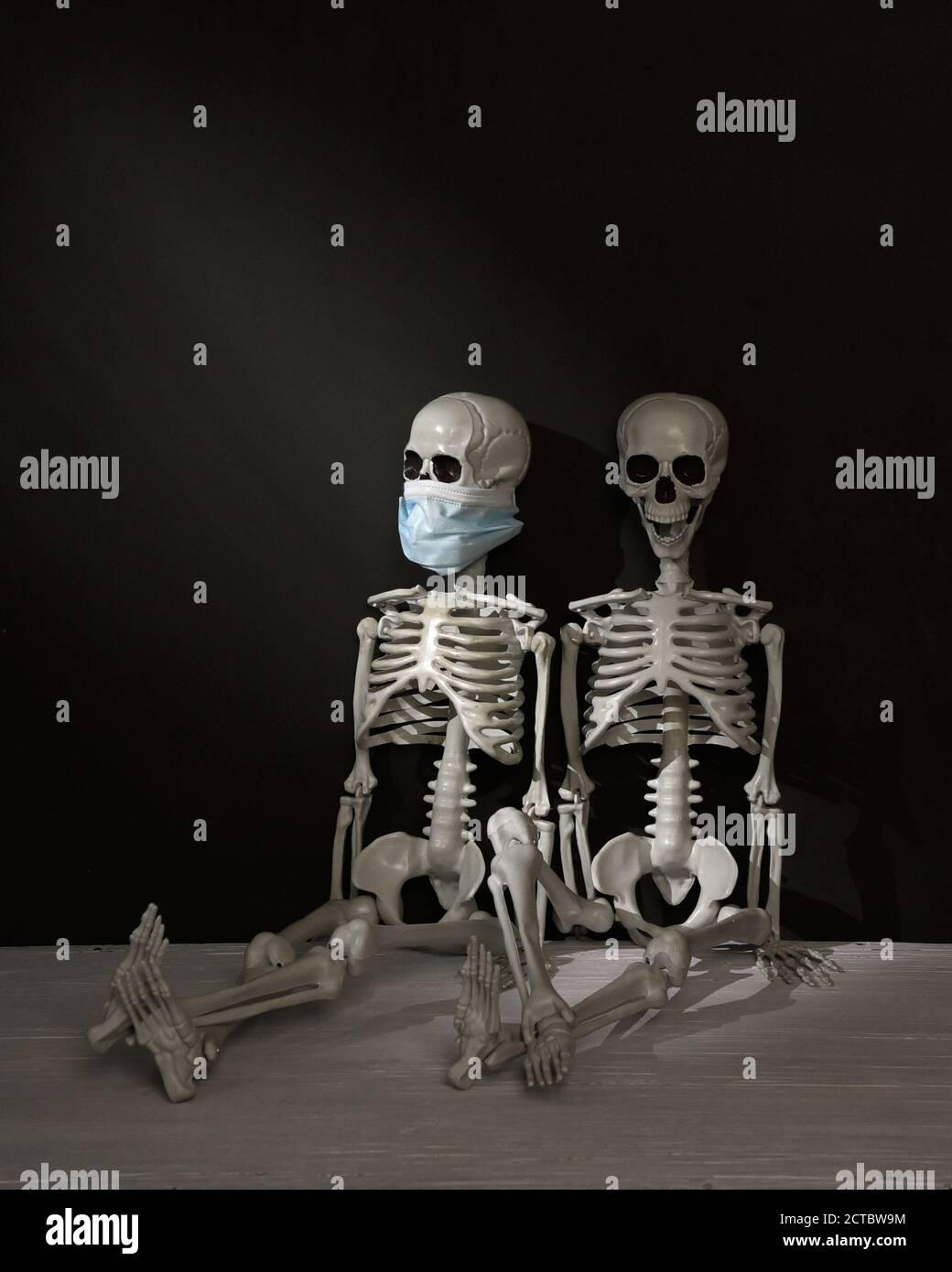 Due scheletri sono seduti in una stanza buia. Uno indossa una maschera e l'altro non è per un concetto di umorismo scuro anti maschera durante la covid 19 pandemia. Foto Stock