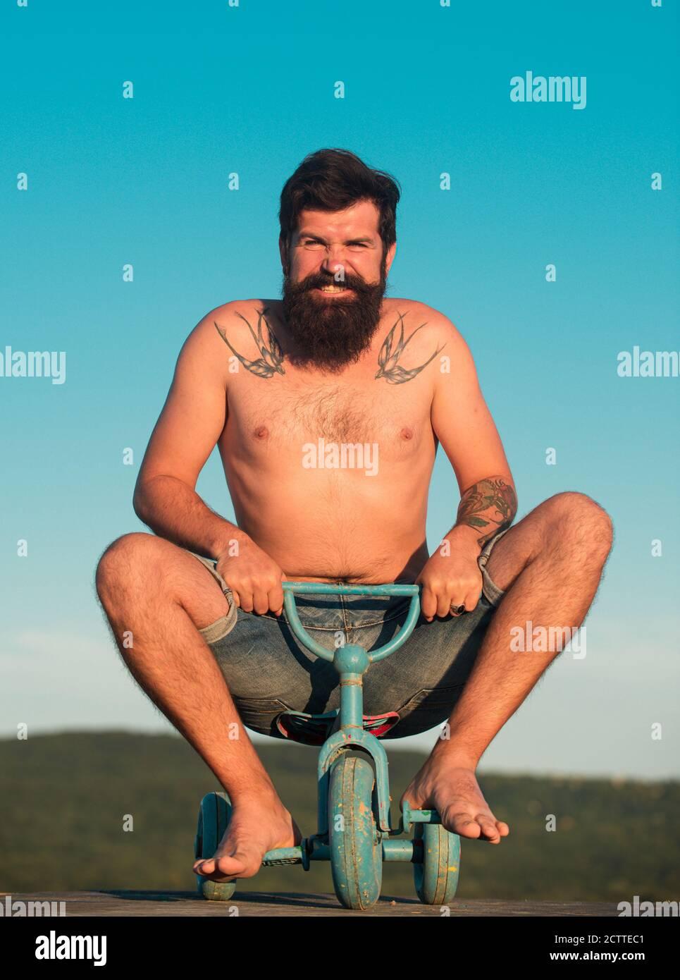 Ragazzo che cavalcano i bambini triciclo. Uomo divertente in bicicletta. Un pazzo emozionale su una moto per bambini. Foto Stock