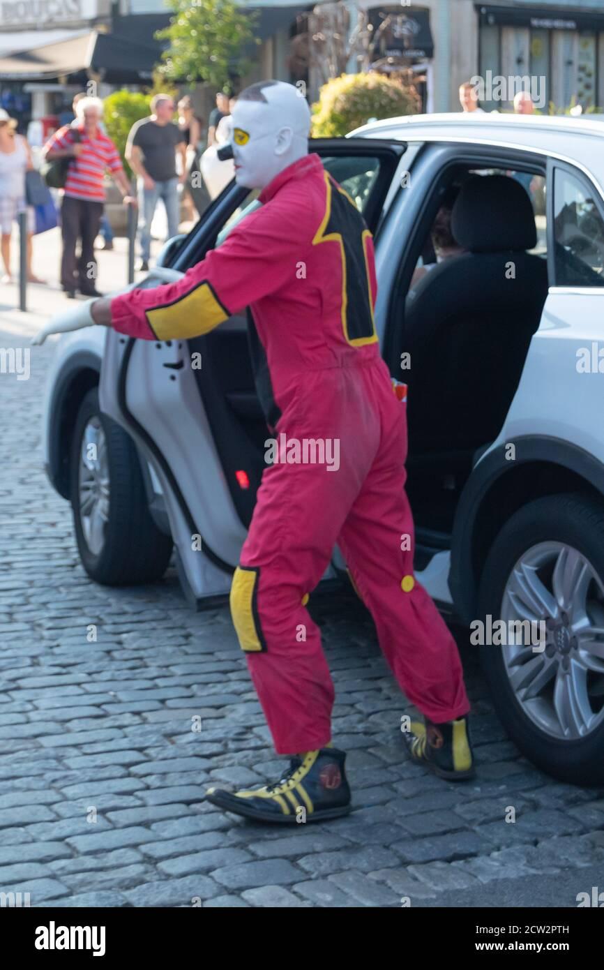Clown in tuta rossa con freccia nella parte posteriore che esce Auto bianca in esibizione di strada alla città di Braga in Portogallo Foto Stock