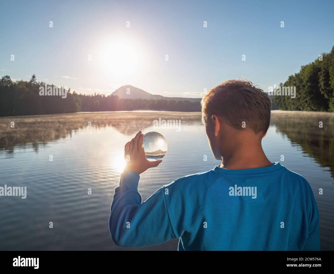 Il ragazzo divertente sta guardando in lente di vetro come il mondo intorno è compresso e capovolto. Foto Stock