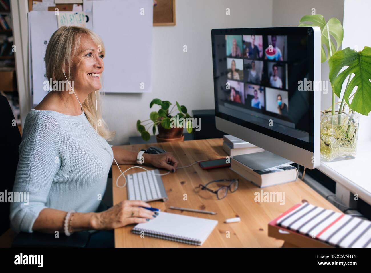 Donna matura sorridente che ha videochiamata via computer l'ufficio domestico. Videoconferenza online per riunioni di team da casa. Donna d'affari attraente Foto Stock
