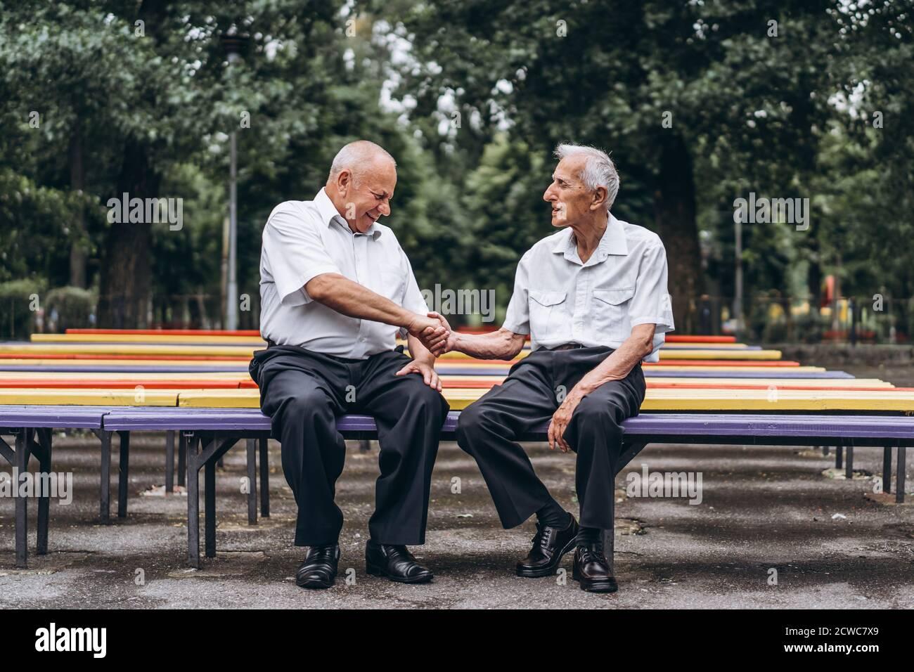 Due anziani adulti hanno una conversazione all'aperto dentro il parco cittadino Foto Stock
