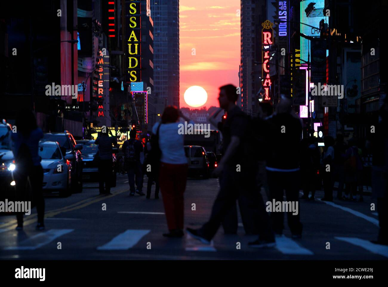 """People stop to view the sunset at 42nd Street during the biannual occurrence named """"Manhattanhenge"""" in New York, May 29, 2013. """"Manhattanhenge"""", named by astrophysicist Neil deGrasse Tyson, occurs when the setting sun aligns itself with the east-west grid of streets in Manhattan, allowing the sun to shine down all streets at the same time. REUTERS/Gary Hershorn (UNITED STATES - Tags: SOCIETY ENVIRONMENT) Foto Stock"""