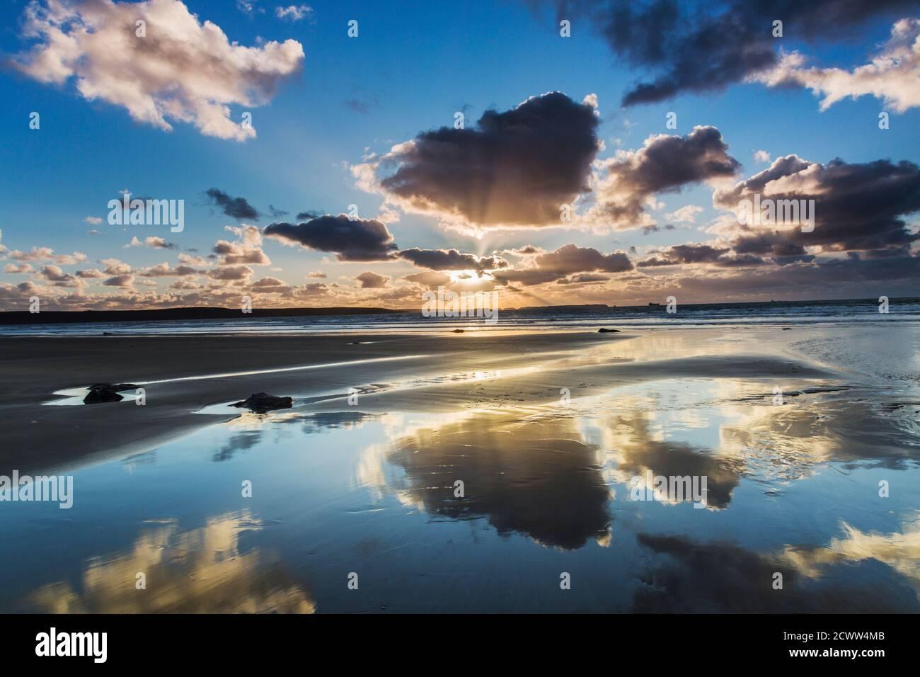 Il cielo al tramonto si riflette nelle sabbie bagnate del spiaggia sotto Foto Stock