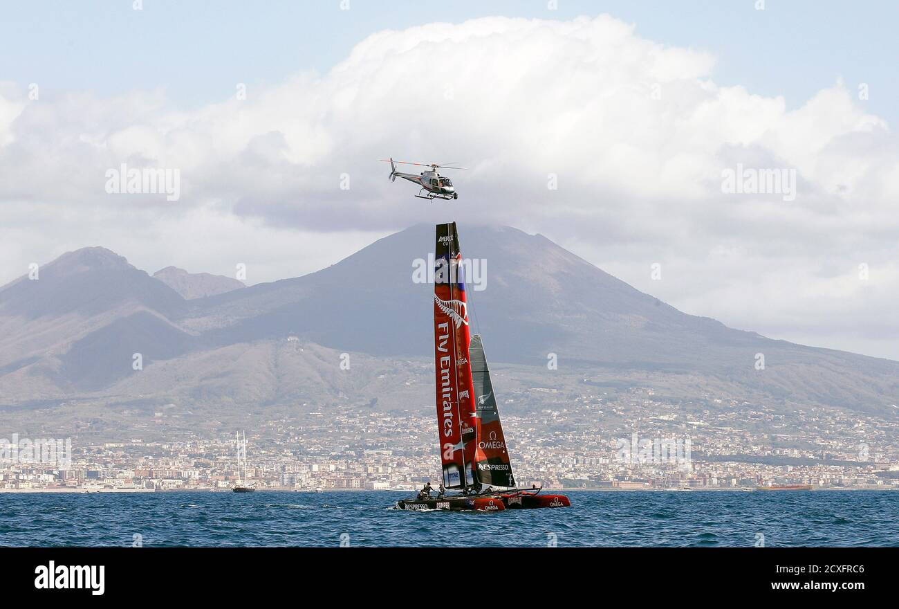 Il team Emirates della Nuova Zelanda gareggia, passando davanti al Vesuvio Vulcan con i loro multiscafi mentre un elicottero sorvola, durante la regata della Coppa del mondo americana a Napoli il 12 aprile 2012. REUTERS/Alessandro Bianchi (ITALIA - Tags: SPORT YACHTING TRASPORTI) Foto Stock