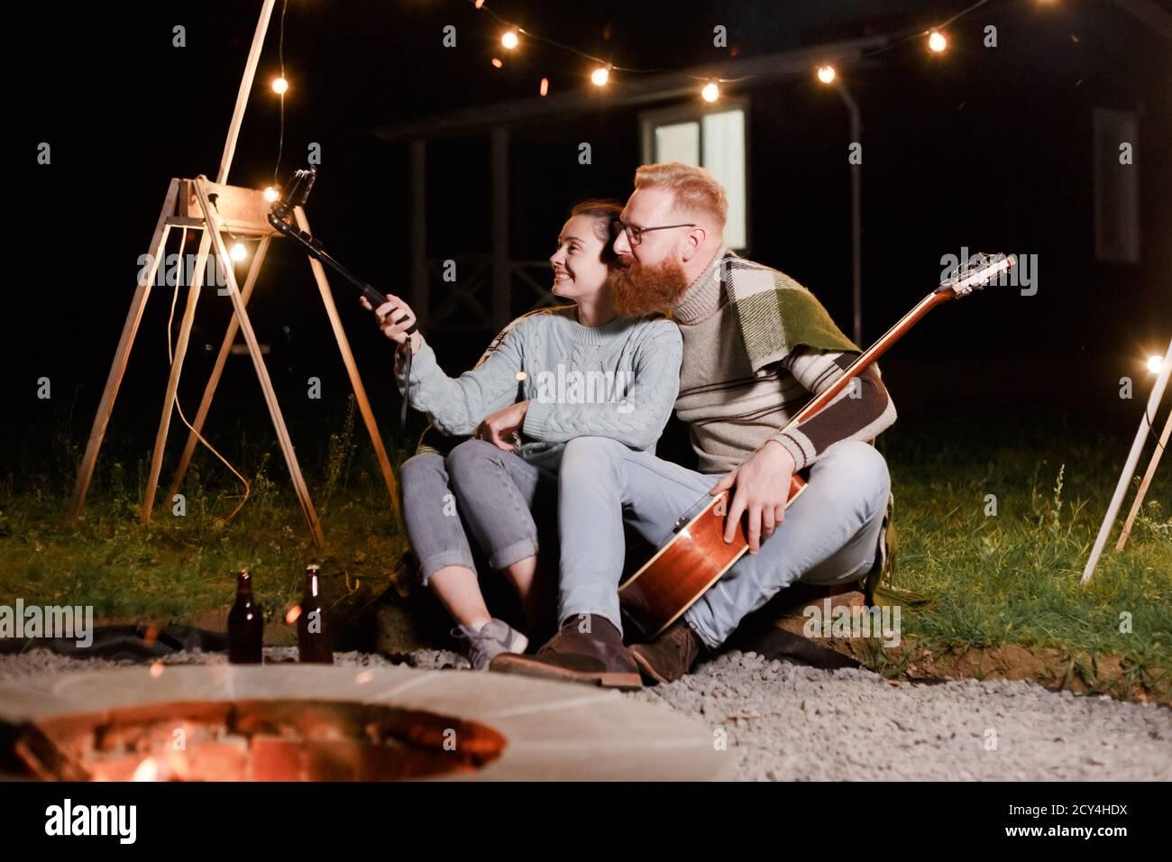 Felice coppia caucasica, donna bruna e uomo bearded con chitarra al picnic in campagna. Divertente coppia che fa selfie, sorridendo e divertirsi insieme Foto Stock