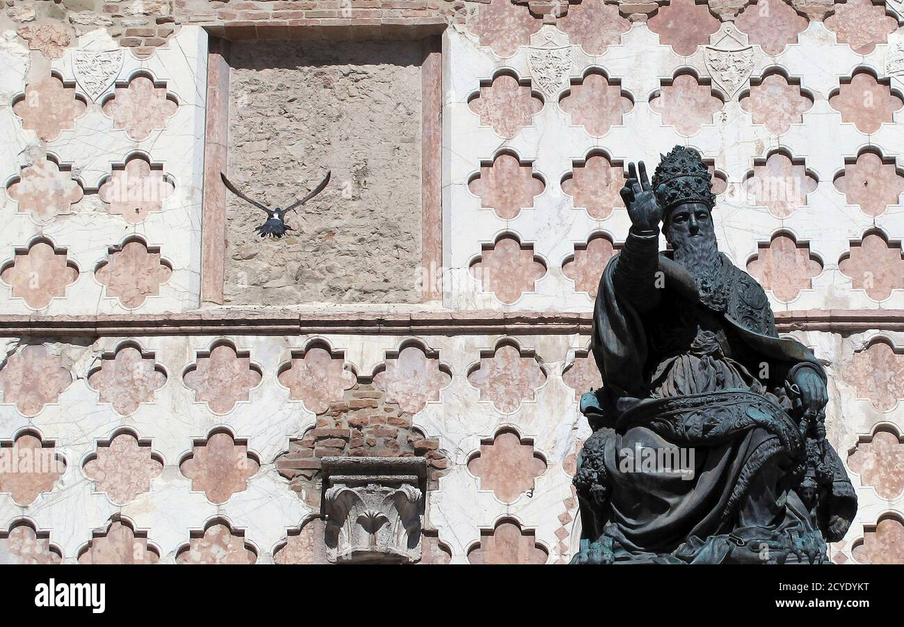 A pigeon flies near the bronze statue of Pope Giulio III, in front of the Cathedral of San Lorenzo, in downtown Perugia October 1, 2011. REUTERS/Alessandro Bianchi (ITALY - Tags: ANIMALS SOCIETY TRAVEL RELIGION) Foto Stock