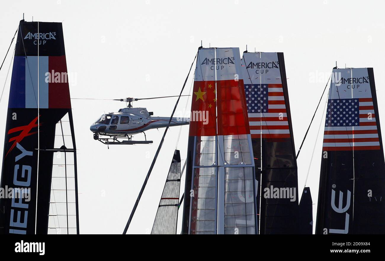 A helicopter flies over the competing multihulls during the America's Cup World Series regatta in Naples April 12, 2012 .  REUTERS/Alessandro Bianchi (ITALY - Tags: SPORT YACHTING TRANSPORT) Foto Stock