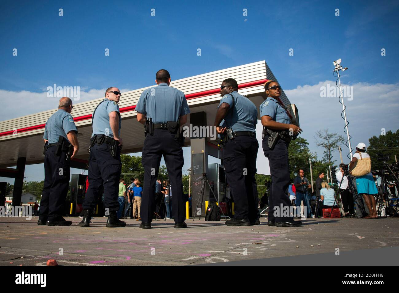 Police officers stand by after the announcement of the name of the officer involved in the shooting of Michael Brown in Ferguson, Missouri August 15, 2014. Police Chief Thomas Jackson on Friday identified Darren Wilson as the police officer who fatally shoot an unarmed black teenager, which led to days of sometimes-violent demonstrations. Jackson announced the name at a press conference held near a QuikTrip convenience store that had been burned amid protests over the shooting of Brown, 18, last Saturday.  REUTERS/Lucas Jackson (UNITED STATES - Tags: CIVIL UNREST CRIME LAW) Foto Stock